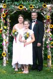 Family wedding portrait. Outdoor wedding portrait of a family of three, standing under an arbor decorated with vines and flowers stock images