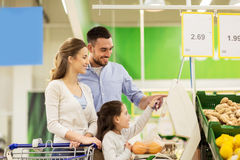 Family weighing oranges on scale at grocery store Stock Photography