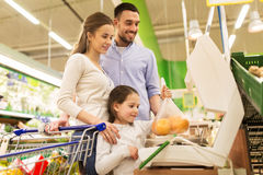 Family weighing oranges on scale at grocery store Royalty Free Stock Photography