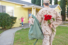 Family Welcoming Husband Home On Army Leave. Happy royalty free stock image