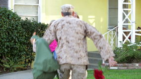 Family Welcoming Husband Home On Army Leave. Family rushes to greet army husband returning on leave - he gives them flowers and they hug. Shot on Canon 5d Mk2 stock video footage