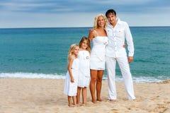 Family in white on beach. Stock Photos