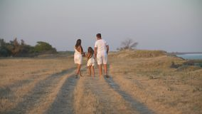 Family in white clothes walks along a dirt road stock video