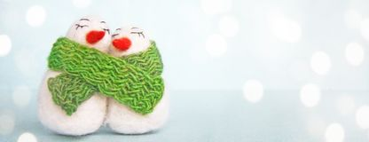 Family of white happy loving felted wool snowmen with green knitted scarf on bright blue background stock images