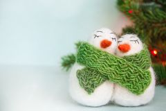 Family of white happy loving felted wool snowmen with green knitted scarf near Christmas tree with lights on bright blue backgroun royalty free stock photo