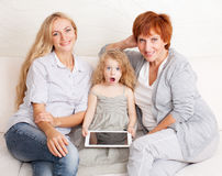Family wiht tablet computer. At sofa. Mother, grandmother and little girl at home on sofa. Generation Stock Image