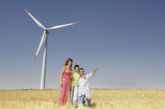 Family and wind turbines. Go for a walk between wind turbines; concept of ecology and alternative energy Royalty Free Stock Photo