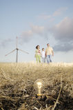 Family and wind turbines, light bulb in the ground Stock Photography