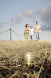 Family and wind turbines, light bulb in the ground. Family and wind turbines; go for a walk between wind turbines; light bulb in the ground, concept of ecology Stock Images