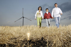 Family and wind turbines, light bulb in the ground. Family and wind turbines; go for a walk between wind turbines; light bulb in the ground, concept of ecology Royalty Free Stock Photos