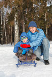 Family in winter. Mother with baby on sled in winter Royalty Free Stock Images