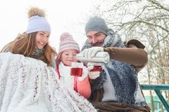 Family in winter drink cup of tea Royalty Free Stock Image