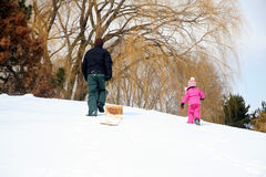 Family Winter Fun. Father and Daughter enjoying a day of fun tobogganing in the snow stock images
