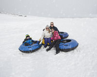 Family winter fun. Sledding and playing in snow Stock Images