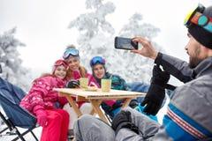 Family at winter holiday making photos. Family at winter holiday in cafe on ski terrain making photos stock photos