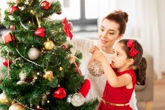 Happy family decorating christmas tree at home royalty free stock photography