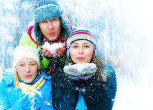 Family In Winter Park. Family Outdoors. Happy Family blowing Snow. Winter Stock Photo
