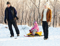 Family  in a winter park. Family walking in a winter park. Parents with child on sled Stock Photos