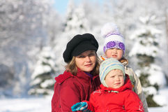 Family in winter park. Happy family (mother with small boy and girl) in winter snow covered city park Stock Photo