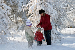 Family in winter park. Happy family (mother with small boy and girl) in winter snow covered city park Stock Images
