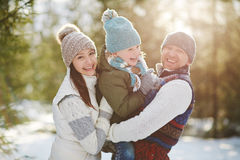Family in winter park. Joyful family of three looking at camera in winter park Royalty Free Stock Photography