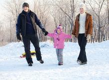 Family  in a winter park. Family walking in a winter park. Parents with child on sled Stock Images