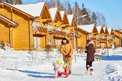 Family in winter resort area. Happy men walking along snowy path with his wife and pulling sled with little kids on beautiful winter afternoon Royalty Free Stock Image