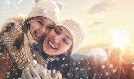 Family and winter season. Happy loving family! Mother and child girl having fun, playing and laughing on snowy winter walk in nature. Frost winter season