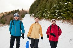 Family in winter together walking in snow Royalty Free Stock Photo