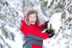 Family winter vacation. Happy smiling boy in beautiful trapper hat at winter enjoying cold weather vacation Royalty Free Stock Photography