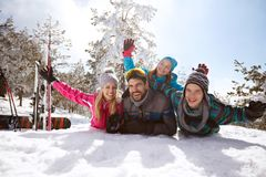 Family on winter vacation lying on snow and enjoy Royalty Free Stock Images