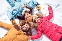 Winter vacation. Family time together outdoors lying smiling happy top view close-up. Family on a winter vacation spending time together outdoors lying on snow royalty free stock images