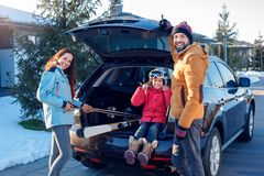 Winter vacation. Family time together outdoors standing near car putting ski equipment into trunk smiling excited stock images