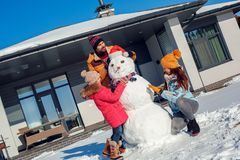 Winter vacation. Family time together outdoors standing near house making snowman smiling concentrated stock images