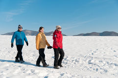 Family in winter walking in snow Royalty Free Stock Photos