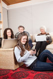 Family with wireless technology. A family at home using wireless technology such as laptop and cell phone royalty free stock images