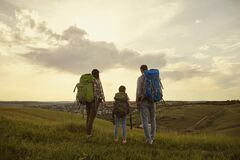 Free Family With Backpacks. Tourists Standing In Nature Hikking At Evening In Evening. Back View. Stock Photo - 186862580
