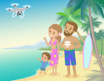 Family woman man mother father and kid child son on seashore with palm serfboard vacation launch drone quadrocopter to take photo Royalty Free Stock Image