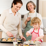 Family women baking cupcakes in kitchen Stock Photos