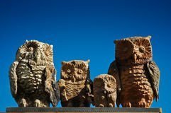 Family of wood owls on background blue sky. A sculpture of family of wood owls local handicraft in Alta Badia, Dolomites - Italy Stock Photo