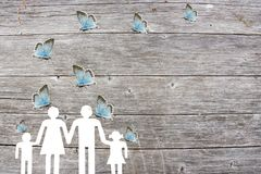 Family on a wooden background with blue butterflies welfare concept.  Stock Photos