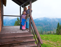 Family on wooden mountain cottage porch Royalty Free Stock Photo