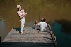 Family on the wooden pier on the lake. Mother is holding in the stock photo