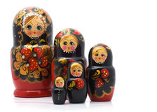 Family of wooden toys. Group of wooden dolls, painted in black, white background Stock Image