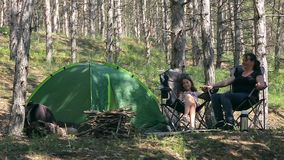 Family in the woods with a tent stock video