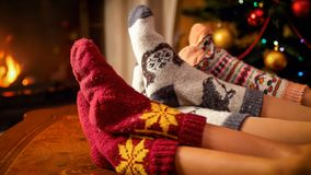 Family in woolen socks holding feet on wooden table next to burning fireplace and Christmas tree. Family in woolen socks holding feet on table next to burning royalty free stock images