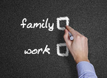 Family and work handwritten with white chalk black background or Stock Photography