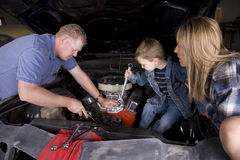 Family working on car stock photo