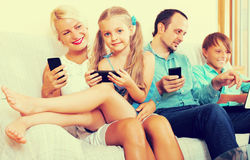 Family working with smartphones. Happy mom, dad and two smiling kids working with smartphones indoors Stock Images