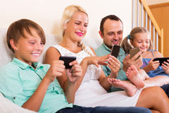 Family working with smartphones. Positive young mom, dad and two happy kids working with smartphones indoors Royalty Free Stock Image